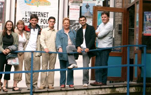 Groupe de jeunes posant devant une affiche