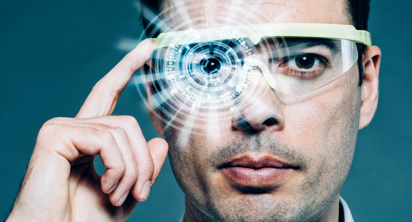 Man wears a pair of futuristic glasses which he adjusts with one finger. In front of his eye is a heads-up display (HUD) that shows lots of data like numbers and structures. It is a concept of augmented reality or a hologram.