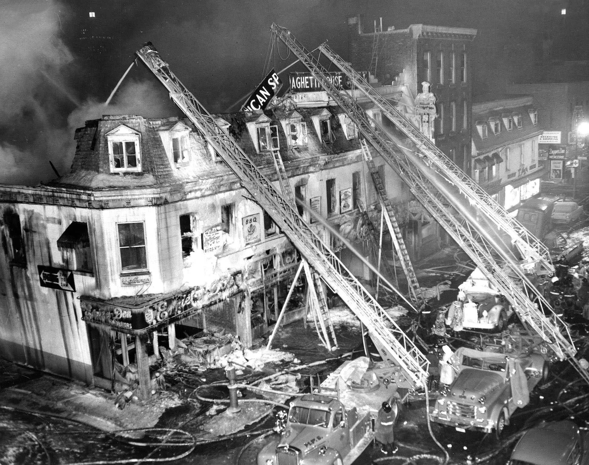 Photographie en noir et blanc montrant les décombres d'un édifice après un incendie. Des camions de pompier sont visibles sur la droite de la photographie.
