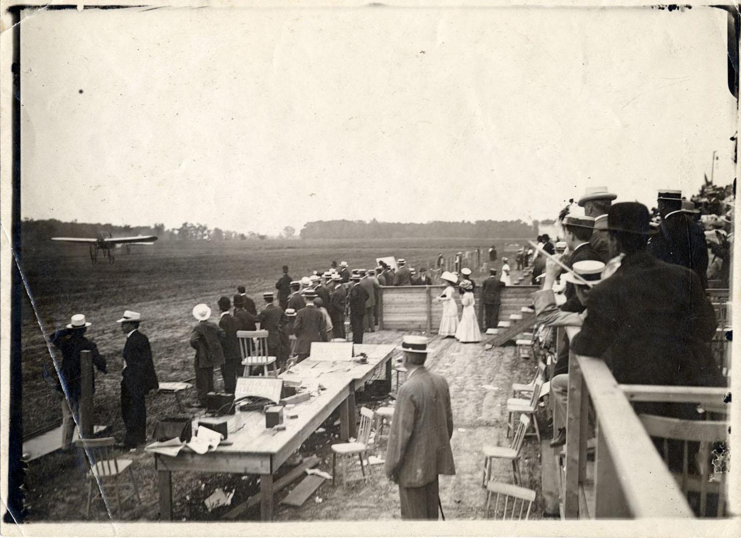 Vue éloignée en plongée, prise des estrades derrière l'équipe de la presse, lors de l'atterrissage du « Scarabée », avec à son bord le comte Jacques de Lesseps, à Pointe-Claire (Lakeside).