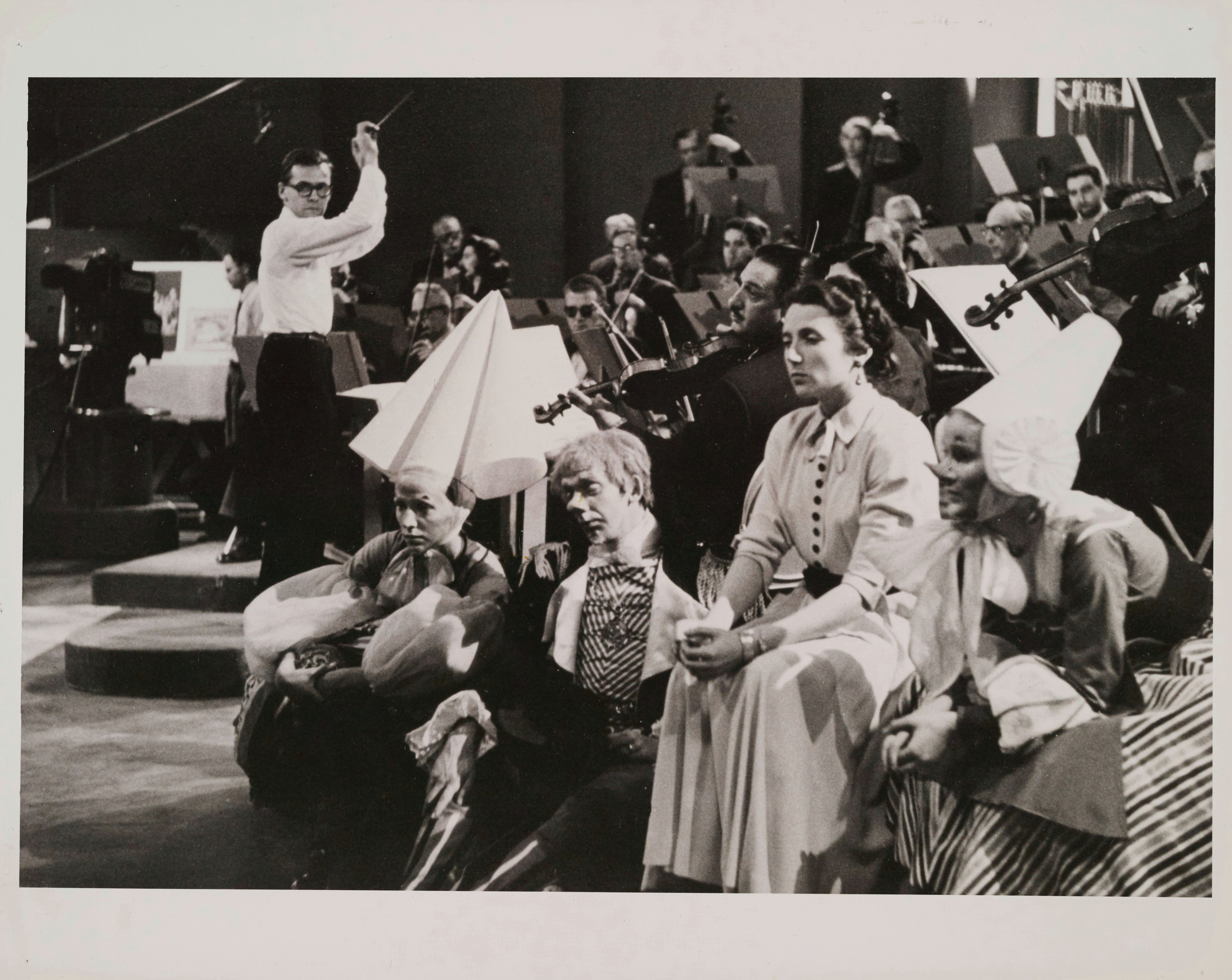 Pierre Mercure dirigeant son œuvre Kaléidoscope à l'Heure du concert, Ludmilla Chiriaeff assise à l'avant-plan.