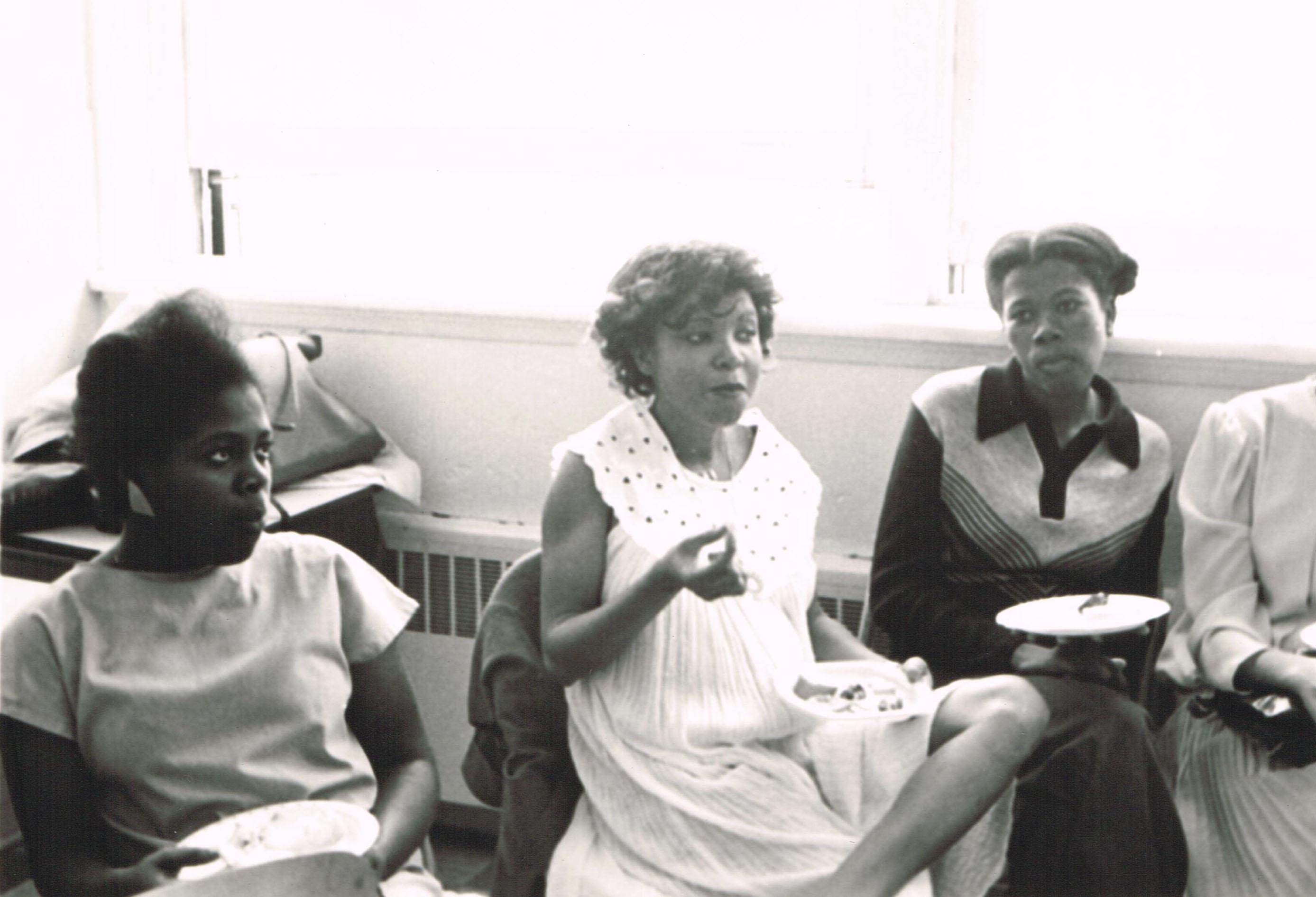 Trois femmes assises tenant une assiette lors d'une rencontre