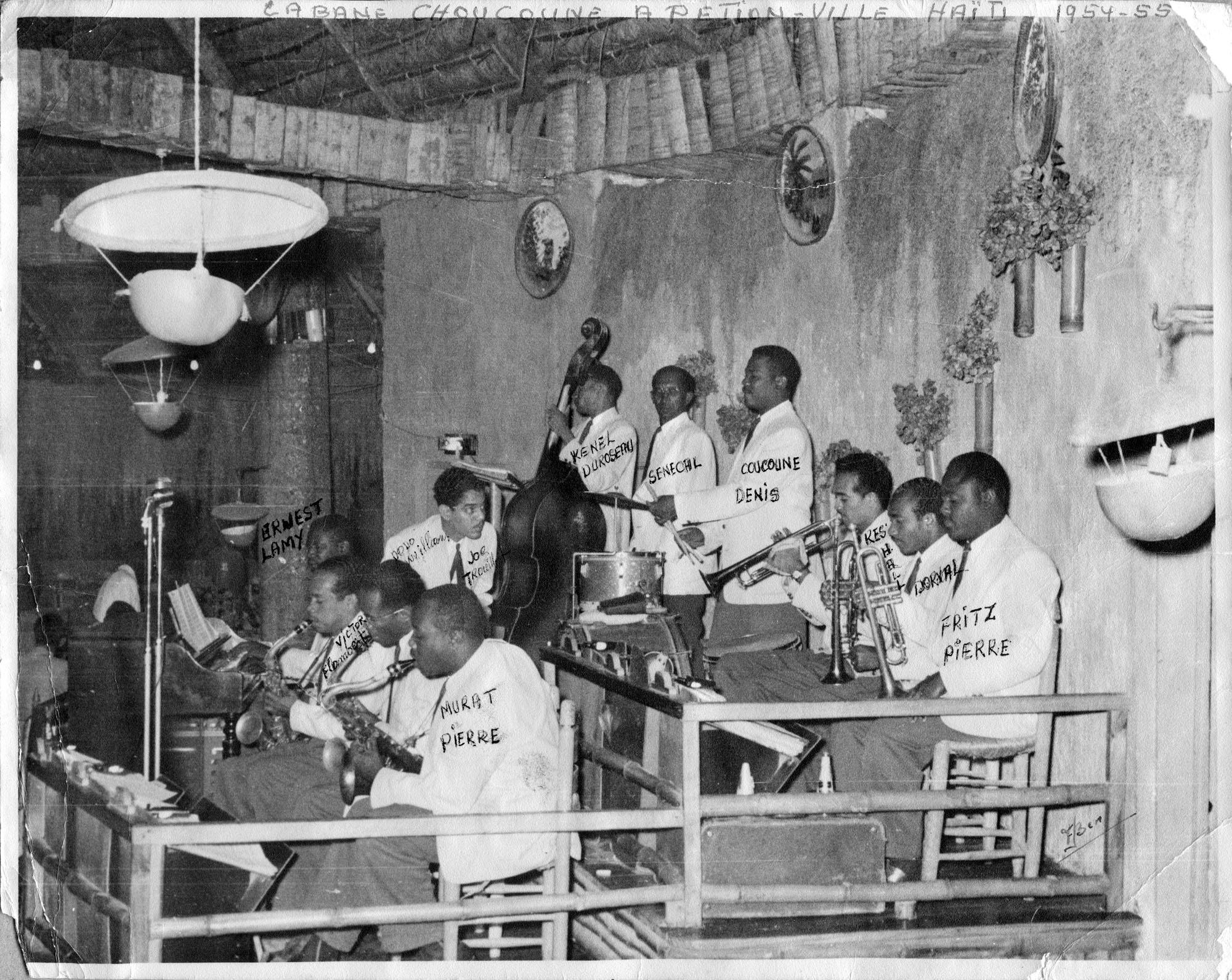 Joe Trouillot est debout entre deux rangées de musiciens dans un cabaret en Haïti.
