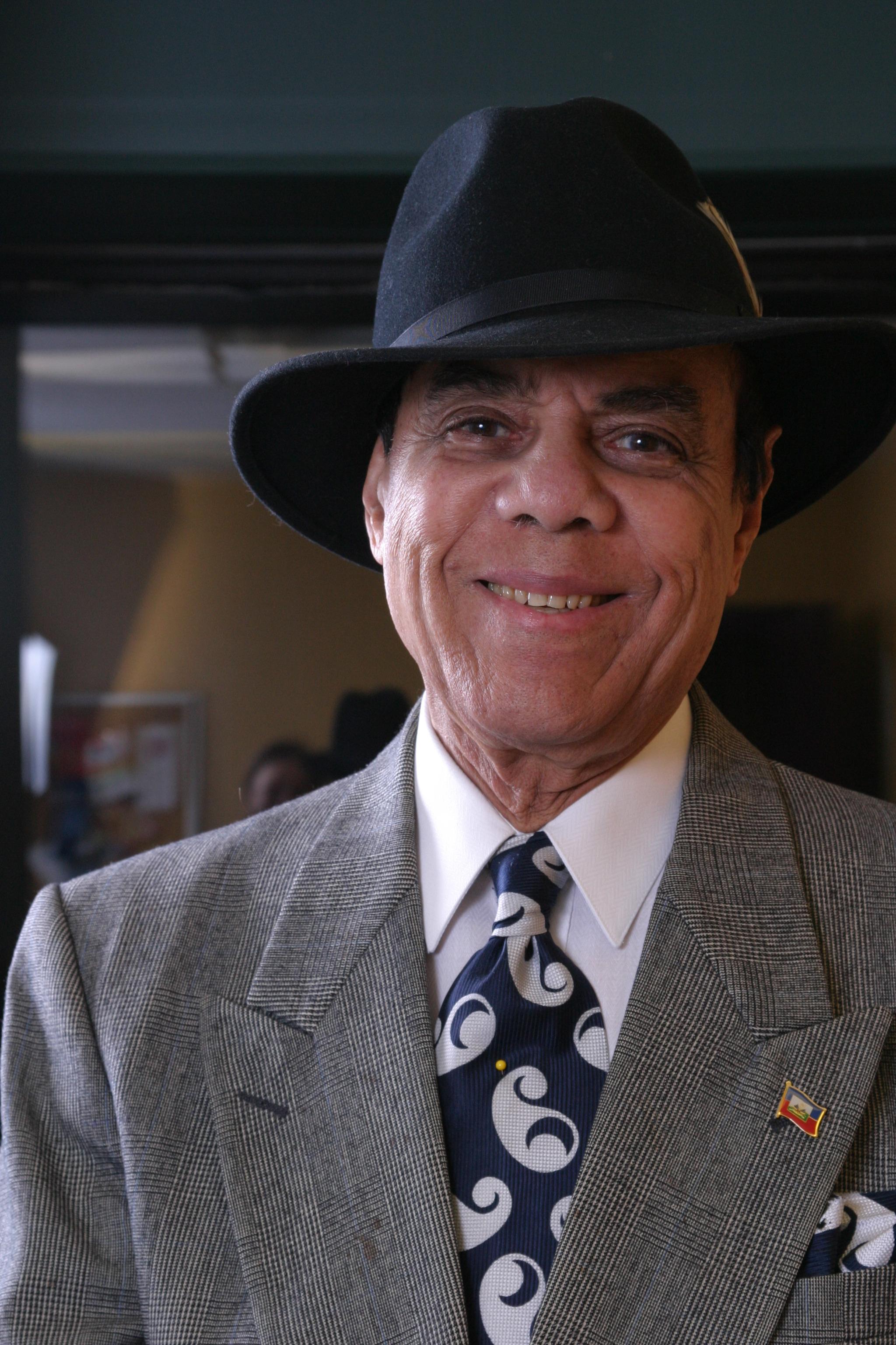 Photo de Joe Trouillot souriant et portant chapeau et cravate.