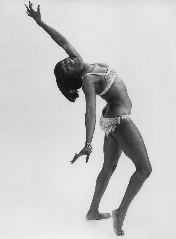 Une jeune femme en costume de scène deux pièces exécute une figure arquée vers l'arrière.