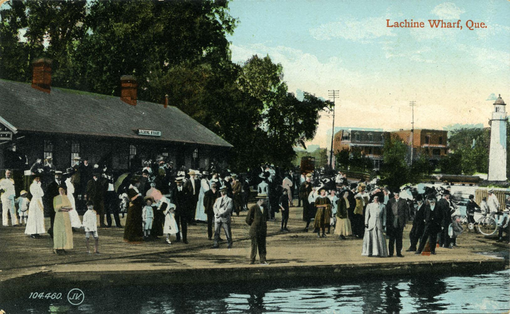 Carte postale colorisée montrant une foule d'hommes, de femmes et d'enfants sur un quai, avec la gare en arrière-plan et des maisons.