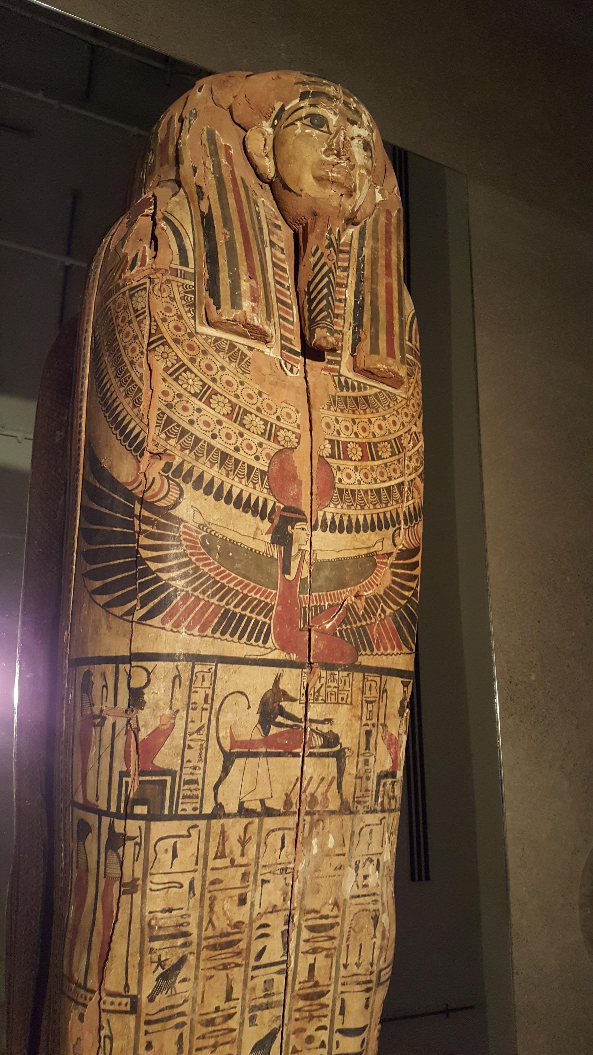 Sarcophage d'Hetep-Bastet présentant une riche décoration sur fond jaune avec de nombreuses divinités peintes, dont Isis aux ailes déployées et Anubis momifiant un corps.