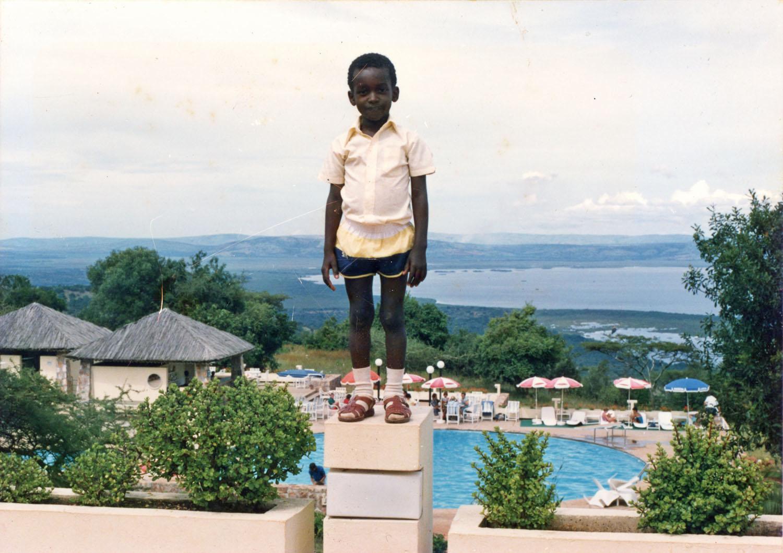 Un enfant juché sur un bloc avec une piscine et un plan d'eau en arrière-plan