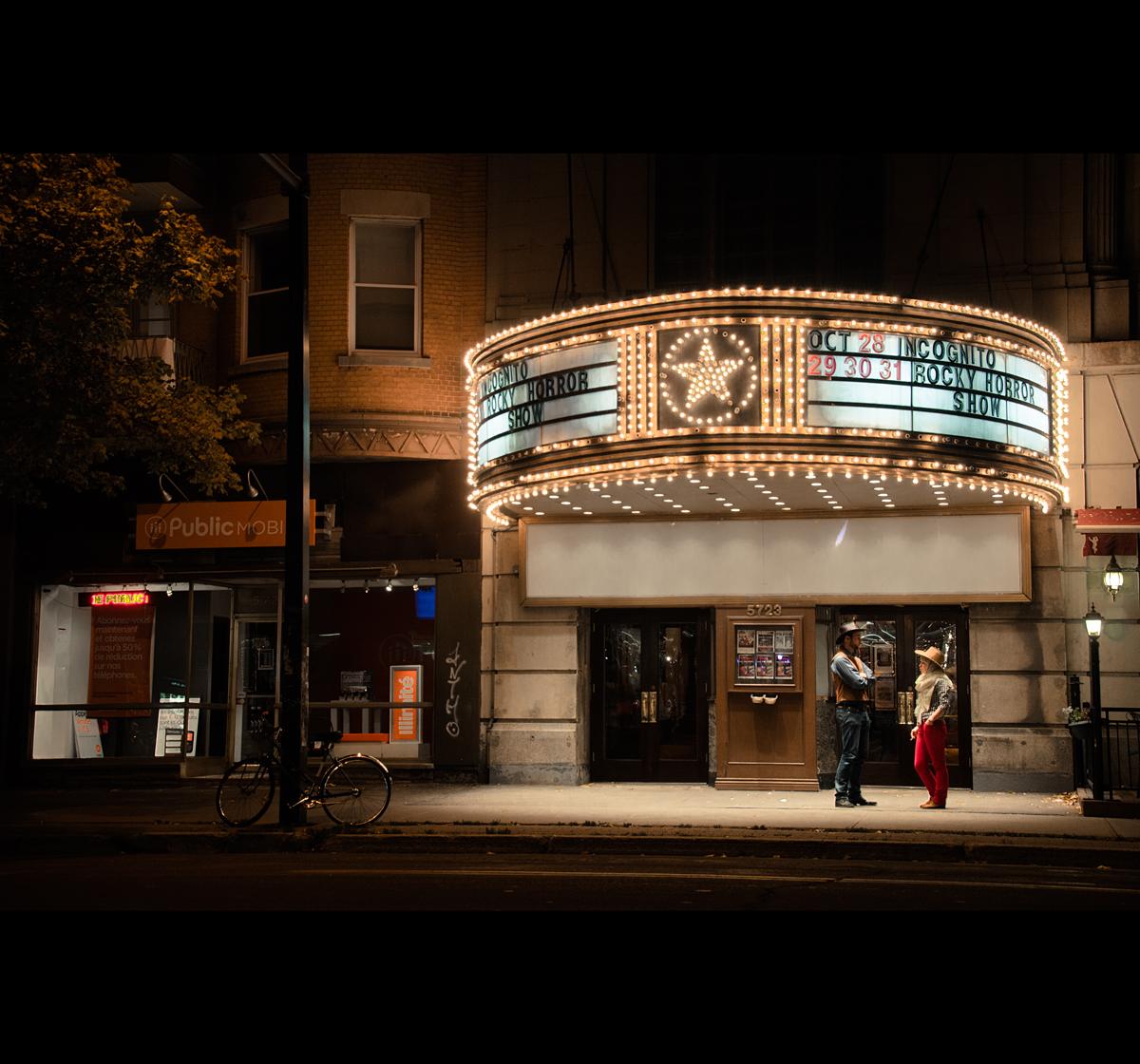 Devanture du Rialto de nuit. Deux personnes sont en discussion devant l'entrée.