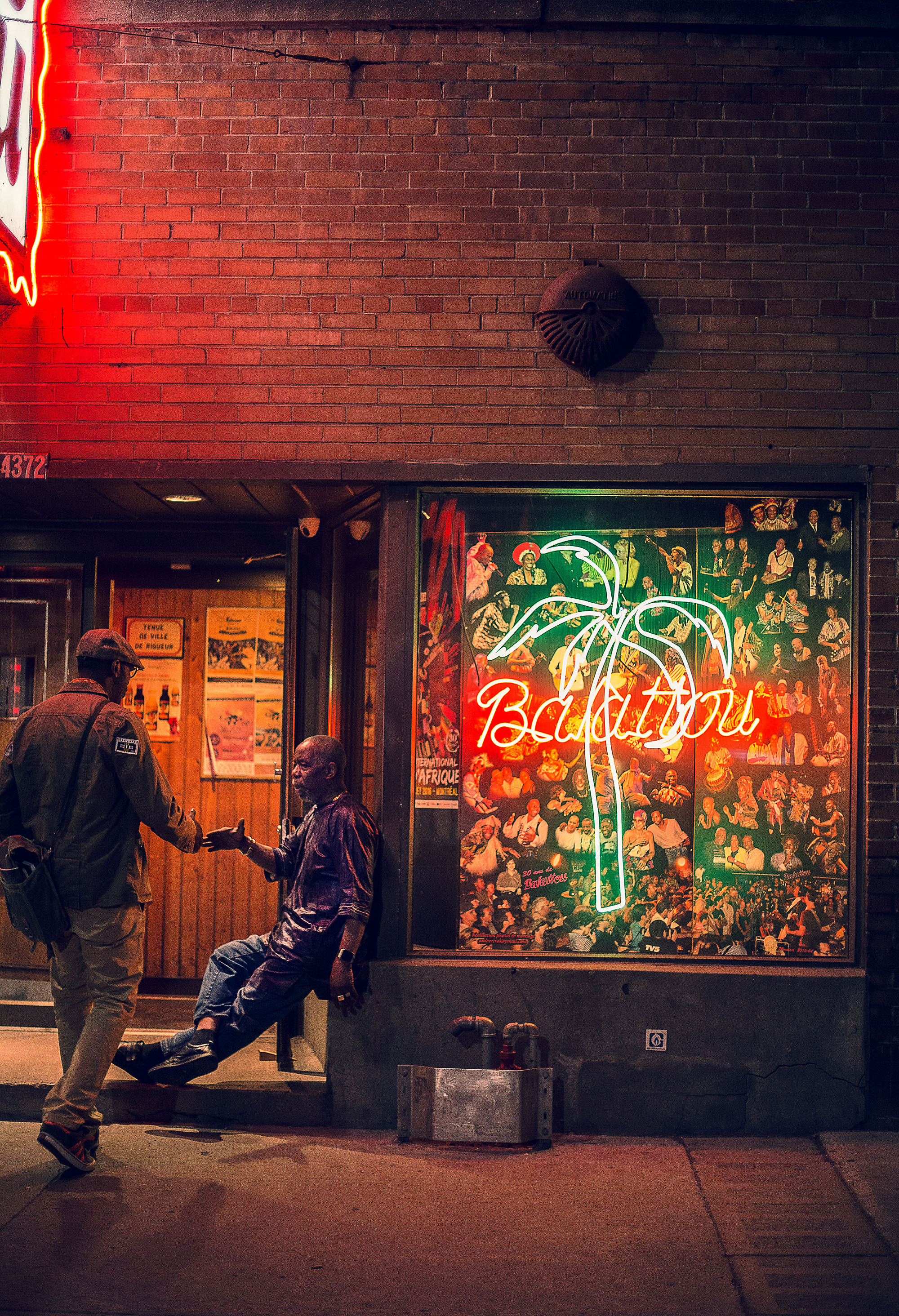 Entrée du Club Balattou de soir, deux hommes se serrent la main