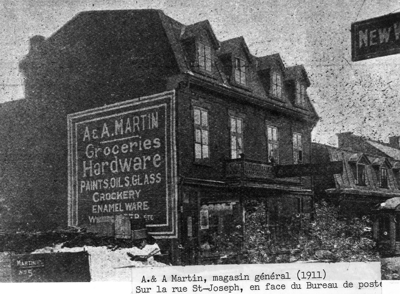 Façade d'un magasin général avec une publicité murale sur le côté du bâtiment.