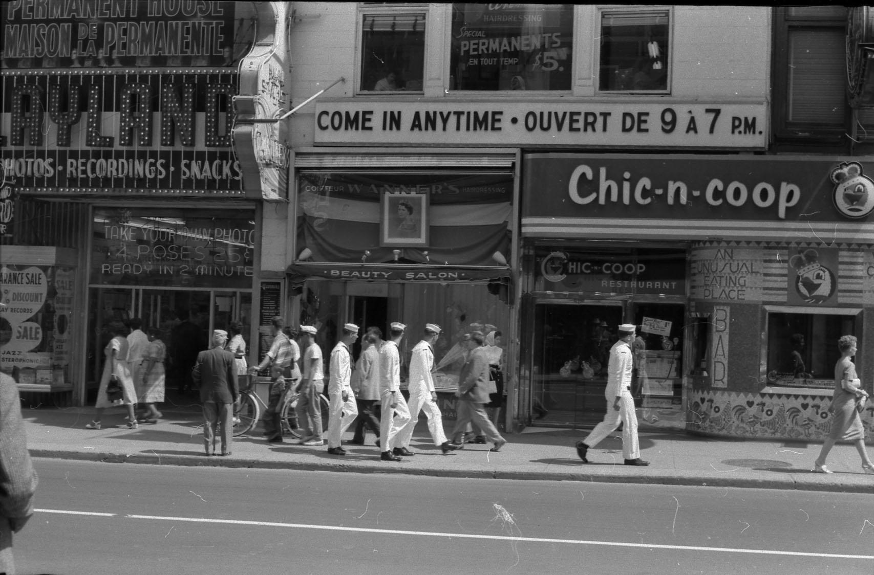 Photo noir et blanc montrant des marins et des passants déambulant rue Sainte-Catherine Ouest dans les années 1950.