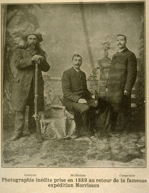Photographie sépia de trois hommes en vêtements civils dans un décor de studio photographique. L'homme de gauche porte un chapeau et s'appuie sur un fusil.