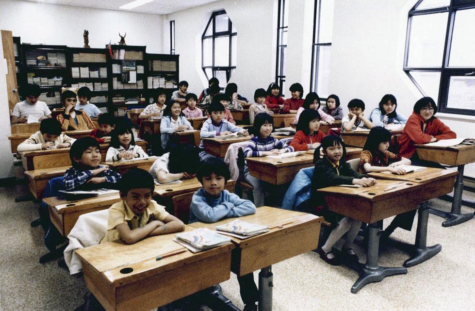 Environ 30 élèves du primaires sont assis à leur bureau.