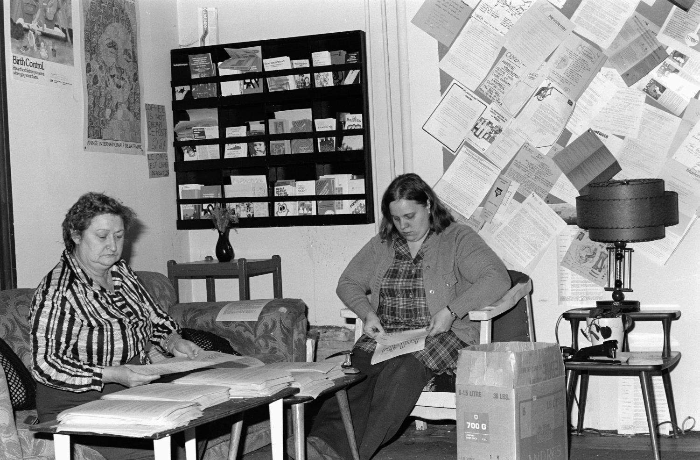 Deux femmes sont assises devant une table basse. Autour d'elles, on voit des affiches sur la contraception et sur l'Année internationale de la femme.