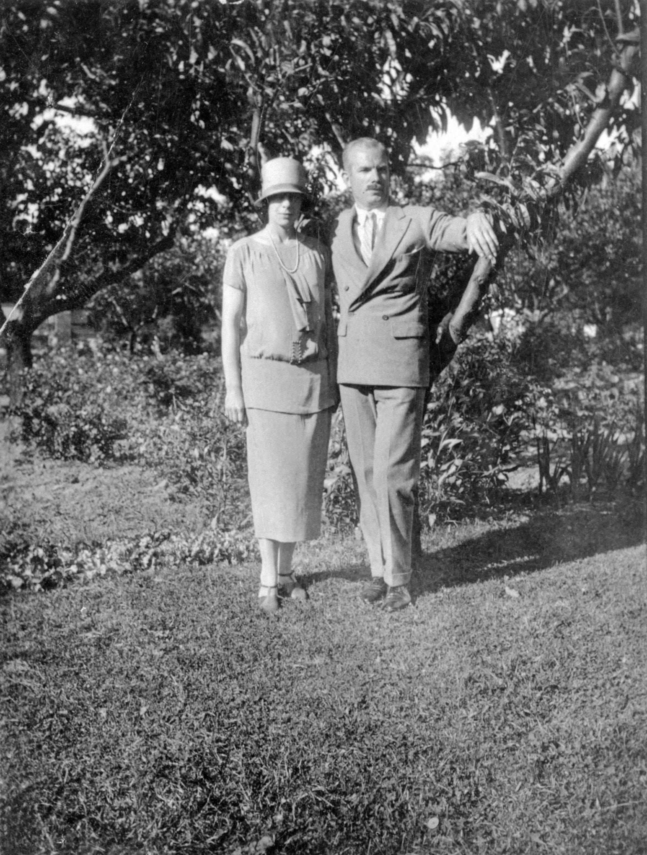 Photo en noir et blanc d'un couple prenant la pose sur une pelouse avec des arbres derrière eux