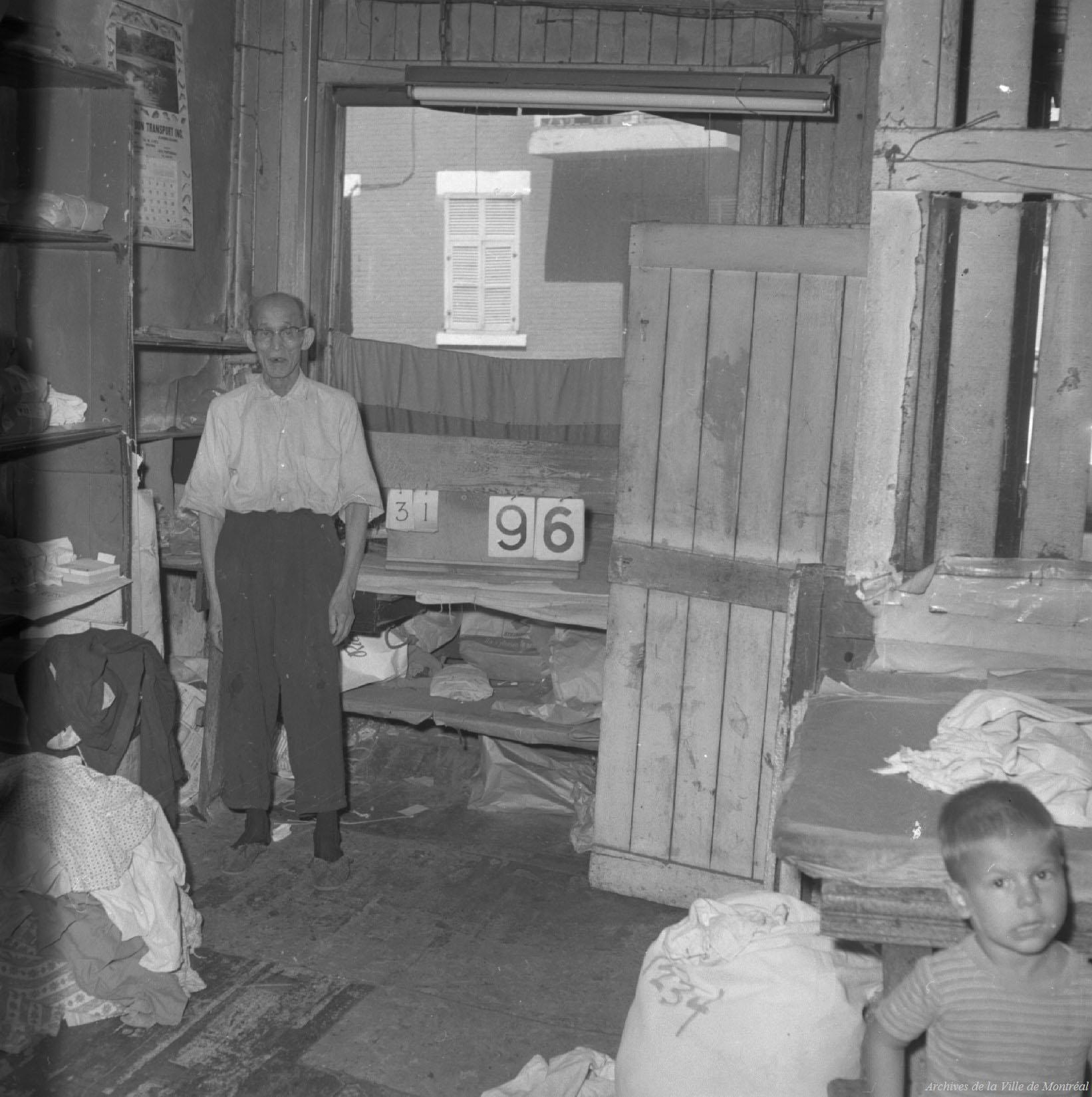 Photo en noir et blanc de l'intérieur d'une buanderie chinoise. Un homme âgé d'origine chinoise est debout au fond de la pièce. On voit un enfant, en partie coupé, dans le coin en bas à droite.