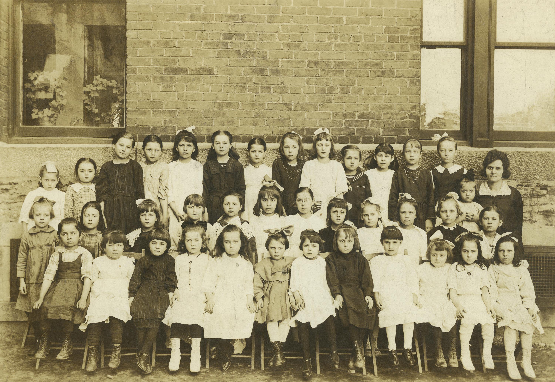 Écolières et leur enseignant posant devant leur école.
