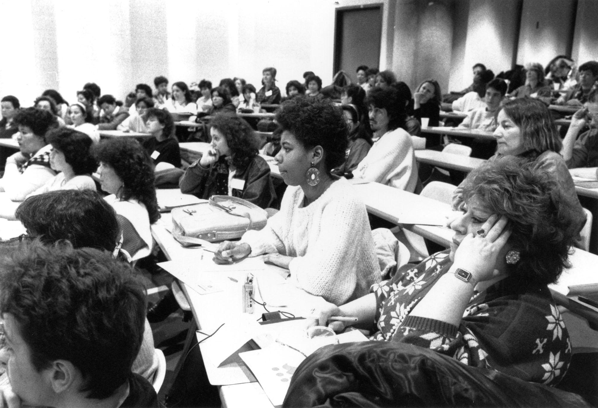 Plus de vingt femmes assises dans une salle de classe.
