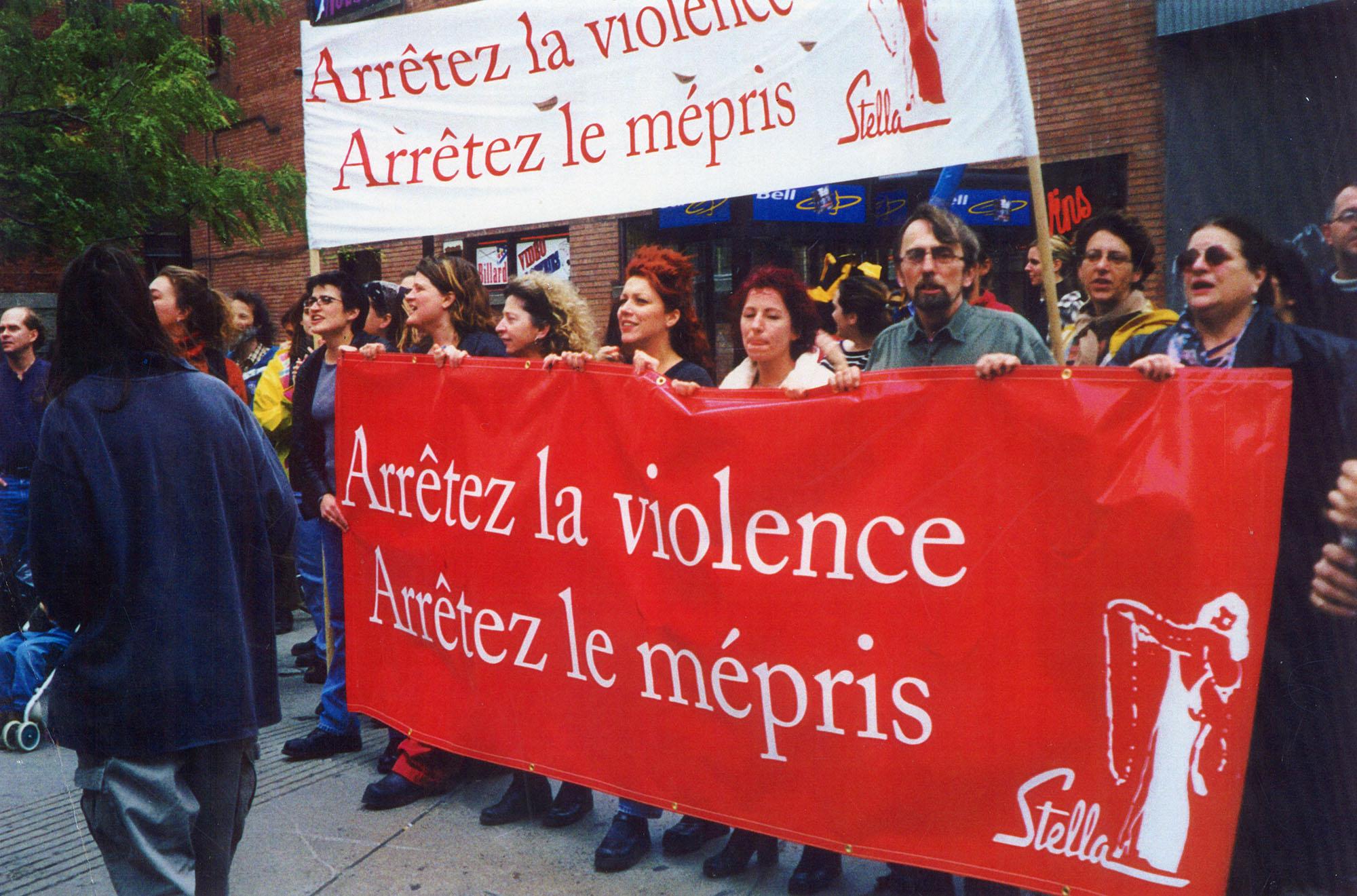 Une quinzaine de personnes se tiennent derrière deux  grandes bannières, l'une rouge, l'autre blanche. On peut y lire : « Arrêtez la violence, arrêtez le mépris, Stella »