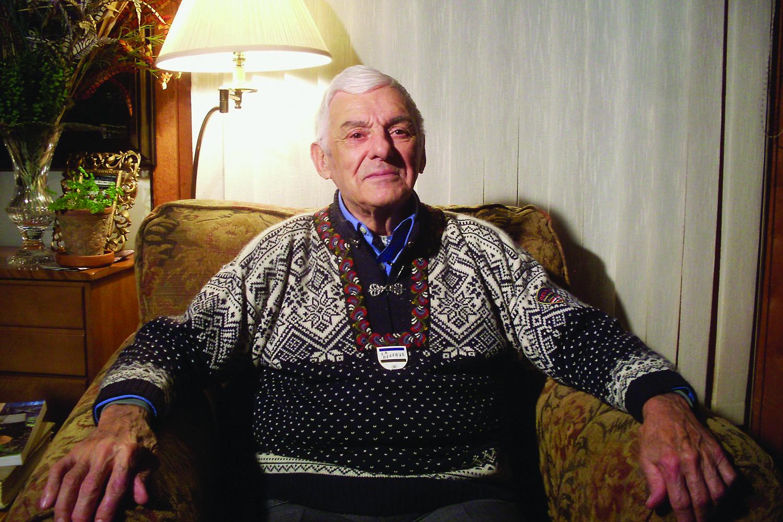 Photographie couleur d'un homme âgé aux cheveux blancs assis dans un fauteuil.