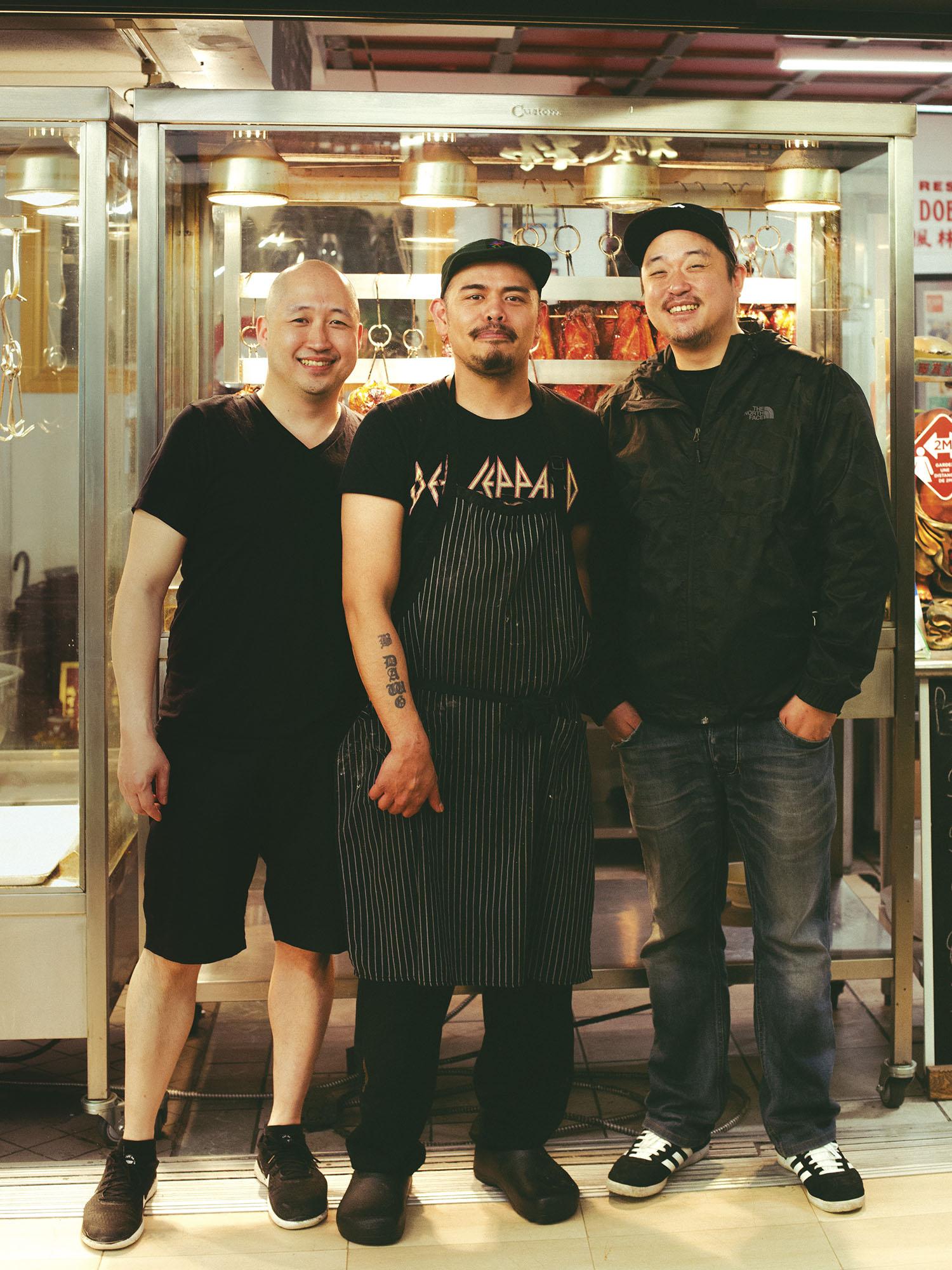 Photo couleur plein pied de trois hommes souriant posant debout devant un restaurant.