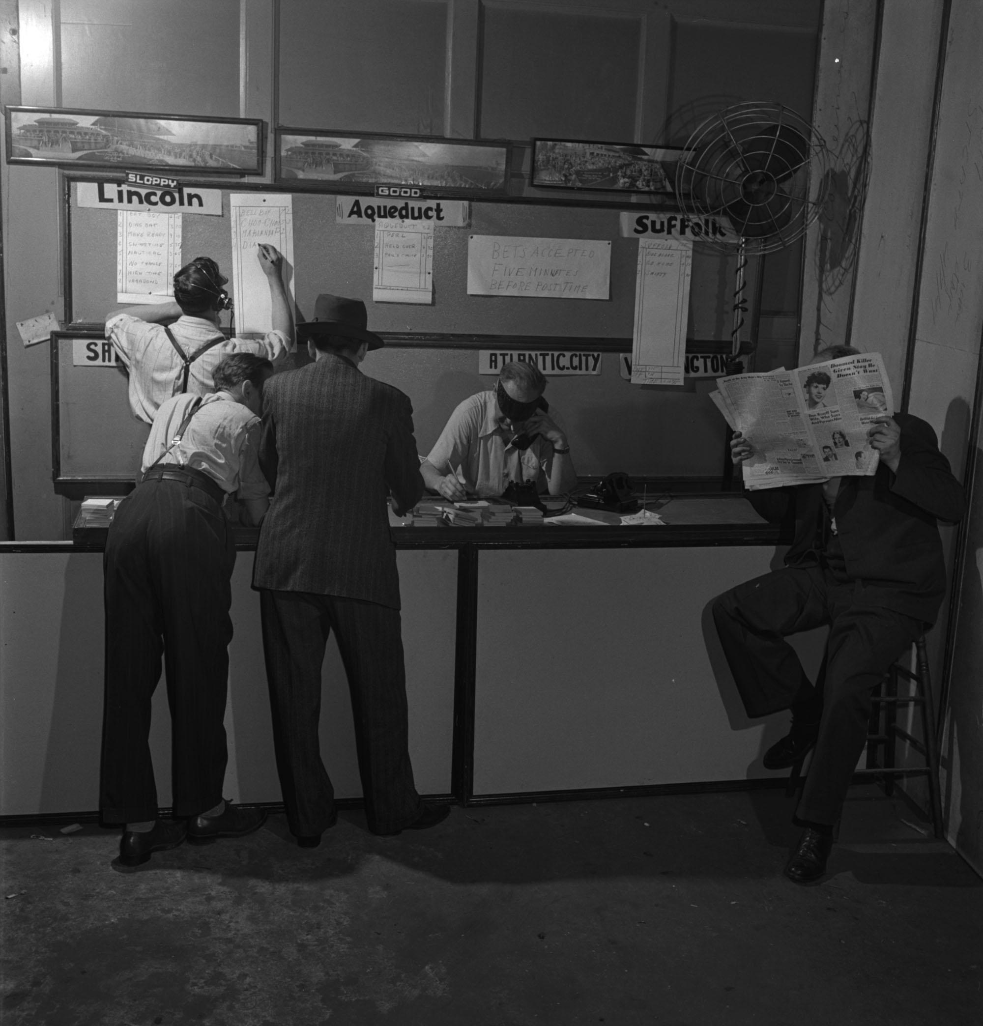 Intérieur d'une maison de paris : deux hommes sont derrière un comptoir, un debout et l'autre assis au téléphone, et trois hommes sont devant, deux debout et un assis avec un journal ouvert devant son visage.