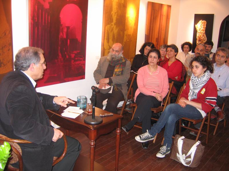 Un homme assis à une table devant un public d'une dizaine de personnes
