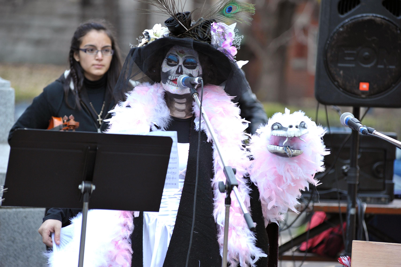 Femme costumée en noir avec un foulard rose tenant devant un micro