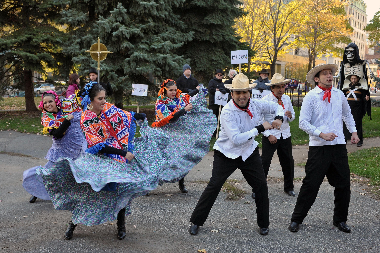 Trois hommes et trois femmes dansent dans un parc en habits traditionnels mexicains