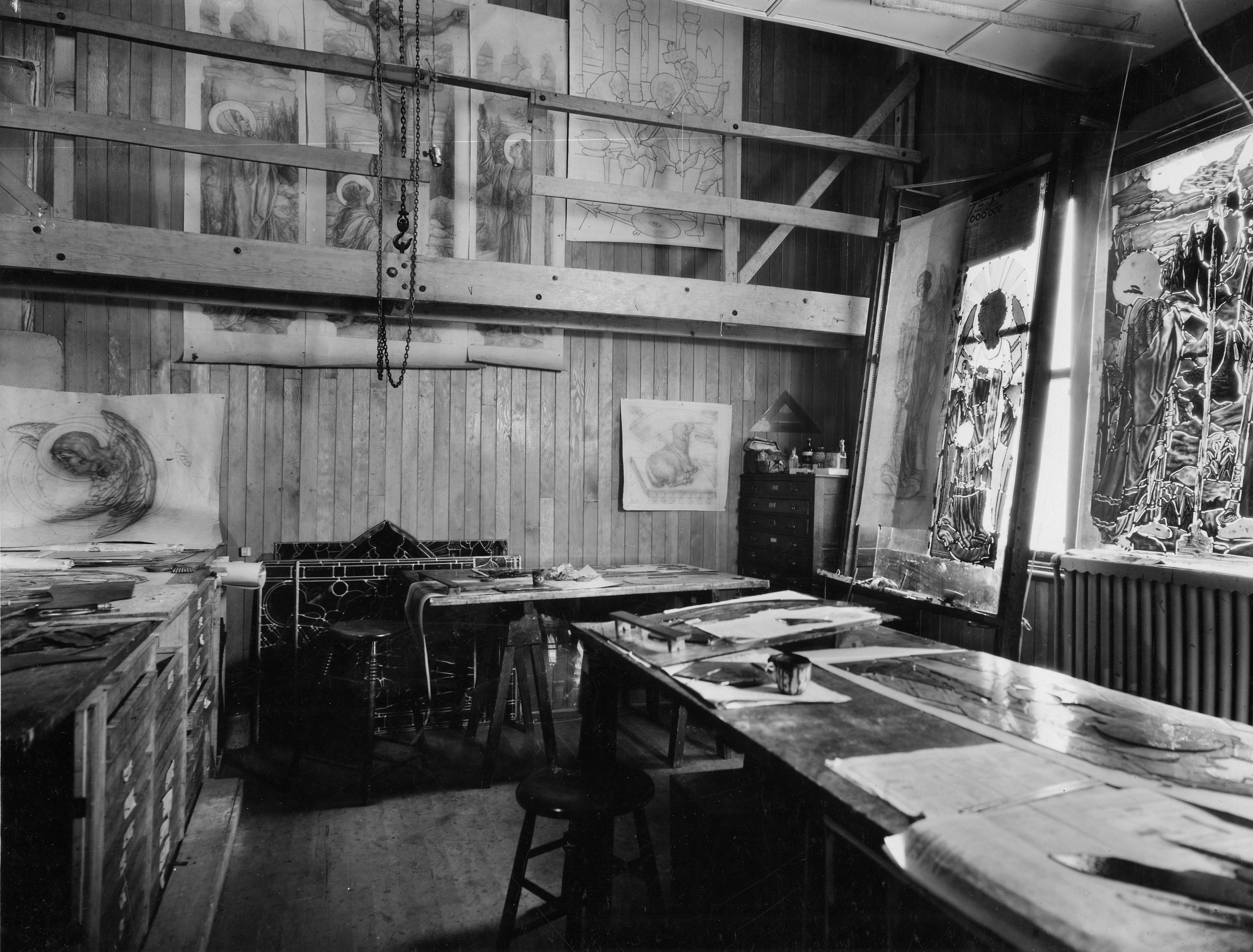 Grande pièce d'un atelier. Plusieurs œuvres sont accrochées au mur ou déposées sur des tables.