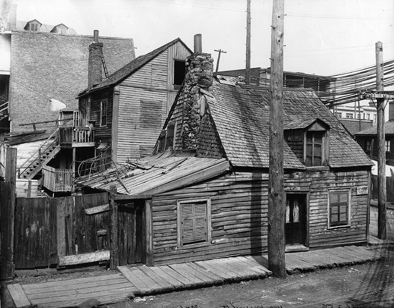 Photographie d'une maison en bois typique du quartier. On remarque que son toit s'affaisse au centre.