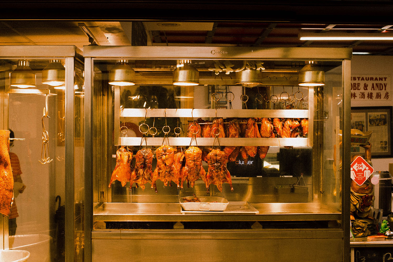 Gros plan sur des poulets barbecue suspendus à la chaleur dans un restaurant.