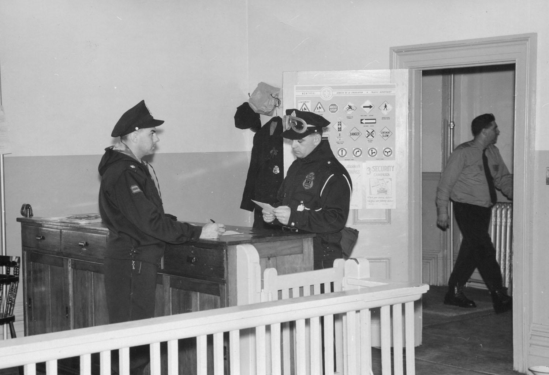 Photographie en noir et blanc montrant deux policiers en uniforme de chaque côté d'un comptoir. Un troisième policier est visible dans le corridor à travers le cadre d'une porte ouverte.