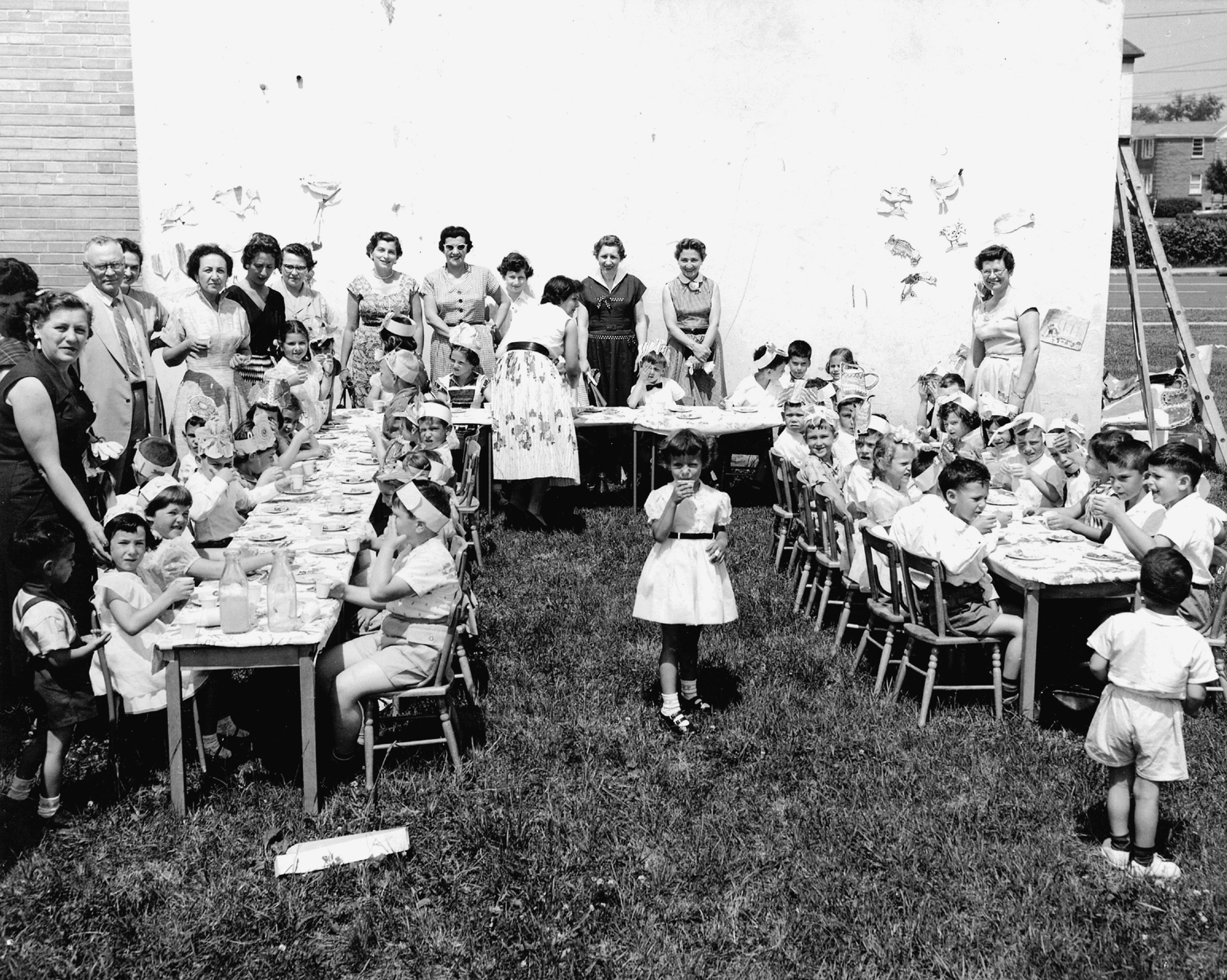 Une cinquantaine d'élèves accompagnés de parents font un pique-nique à l'extérieur.