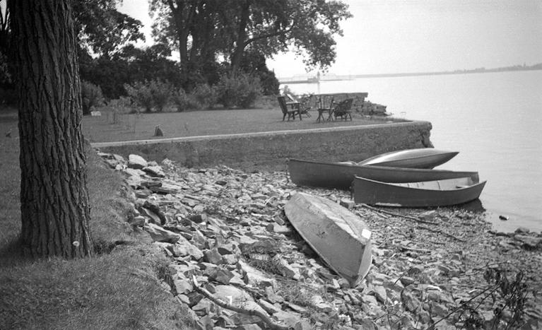 Berges naturelles avec des chaloupes et une terrasse surélevée sur laquelle se trouvent des chaises et une table, à proximité du lac.