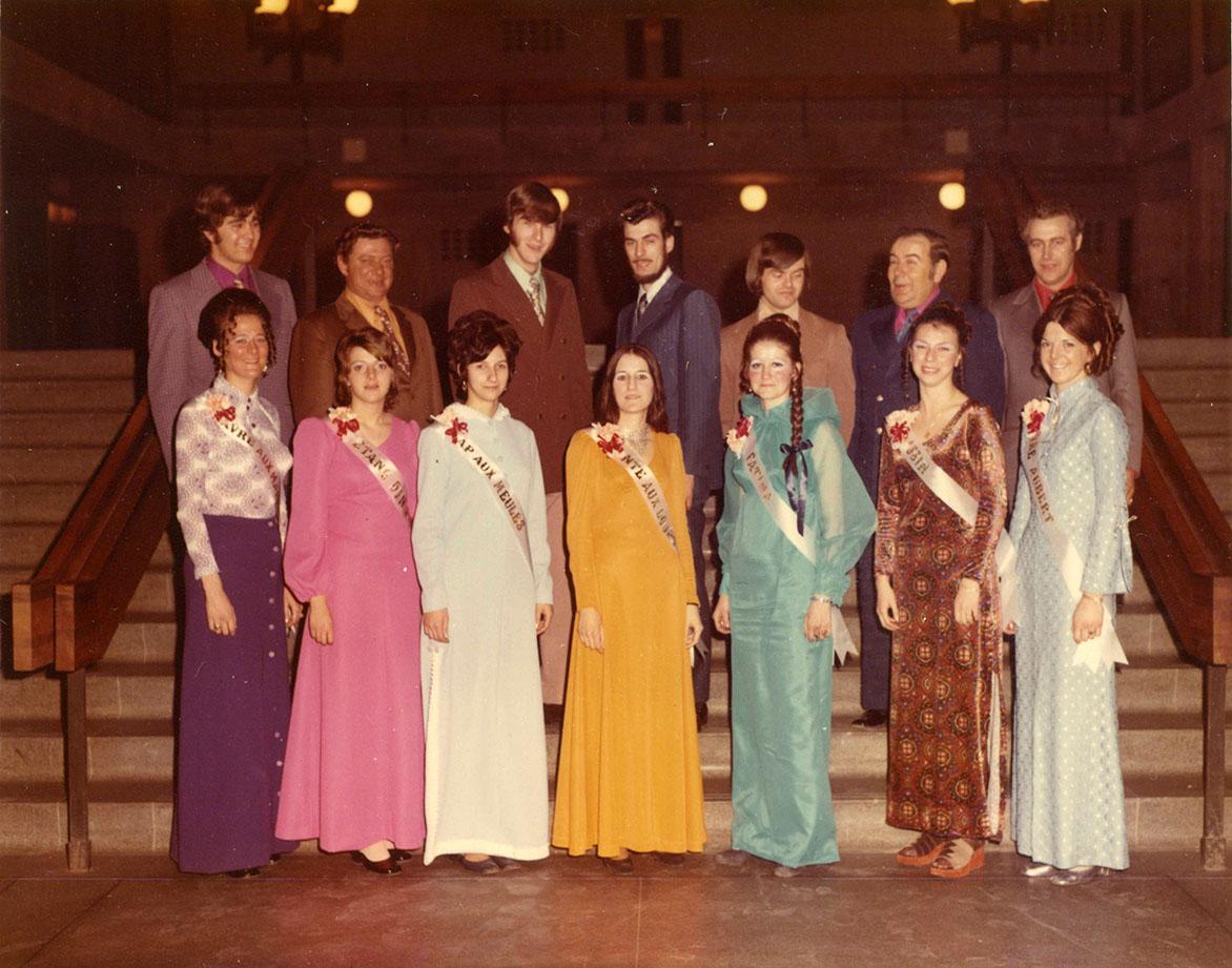 Sept jeunes femmes sont debout. Derrière chacune d'entre elles, un homme est debout.