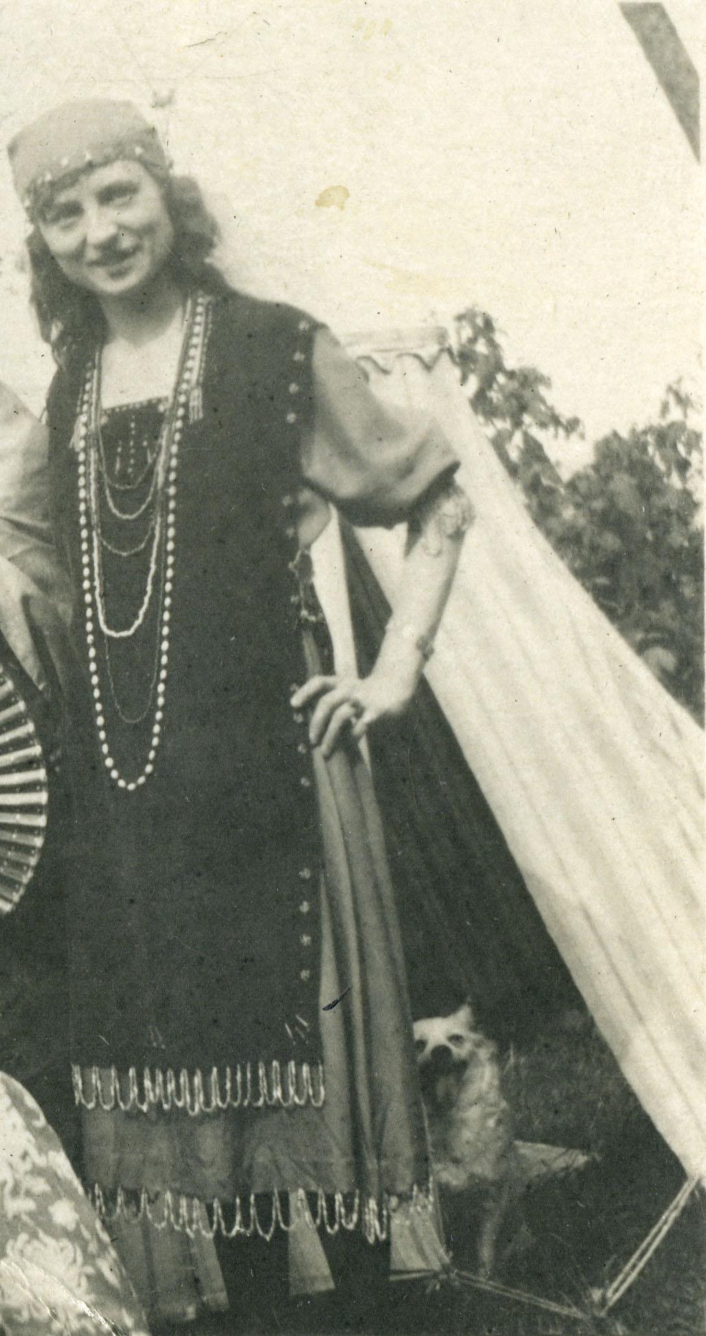 Jeune femme coiffée d'un foulard et portant une robe bohémienne et plusieurs colliers, devant une tente et un chien.