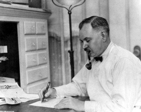Ernest Ouimet travaillant à un bureau en fumant la pipe