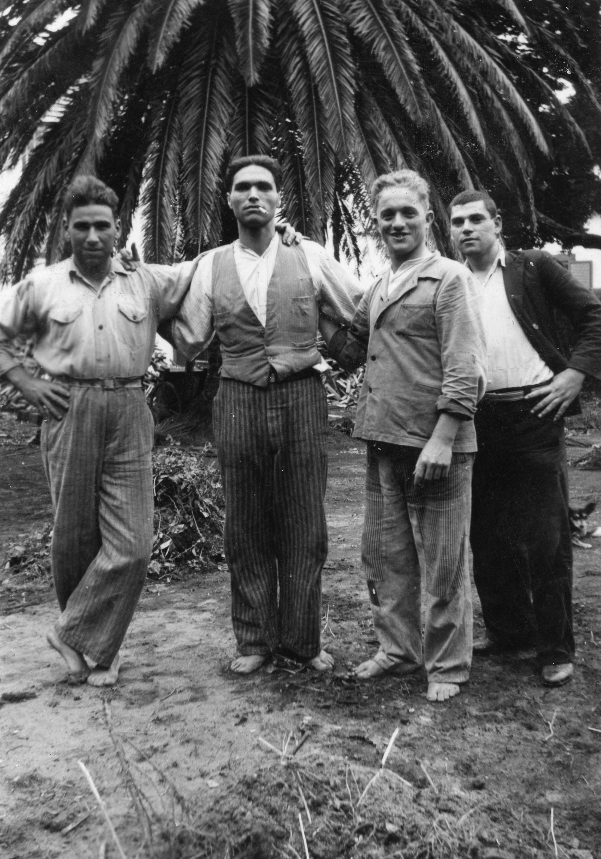 Photo en noir et blanc de quatre hommes, debout, devant un arbre. Un seul porte des chaussures.