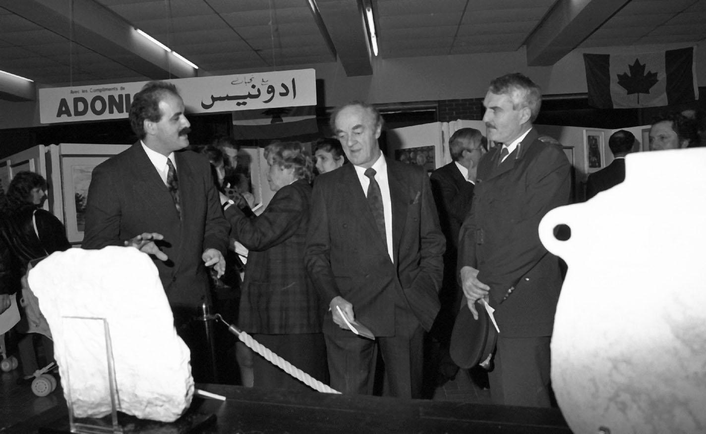 Trois hommes se tiennent devant des objets exposés. Derrière, une affiche du Marché Adonis.