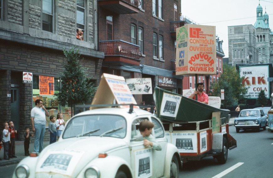 Deux voitures circulent sur une rue. Une remorque est attachée à l'une d'elles. Des affiches sont placardées sur une voiture et sur la remorque. Un homme tient une affiche dans la remorque. Un homme et des enfants sont sur le trottoir.