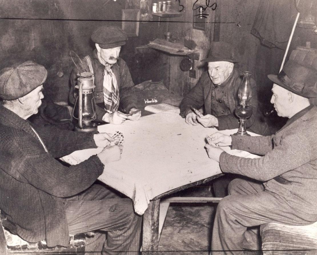 Quatre hommes âgés assis autour d'une table jouent aux cartes