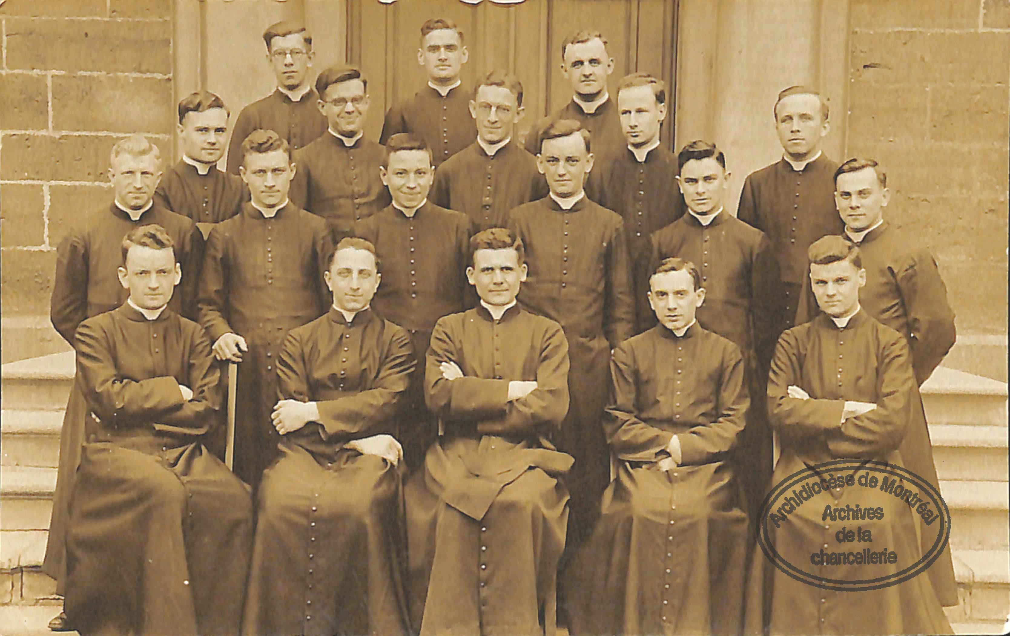 Photographie de groupe des jeunes prêtres posant devant le séminaire à Montréal. Paul-Émile se trouve en avant au centre.