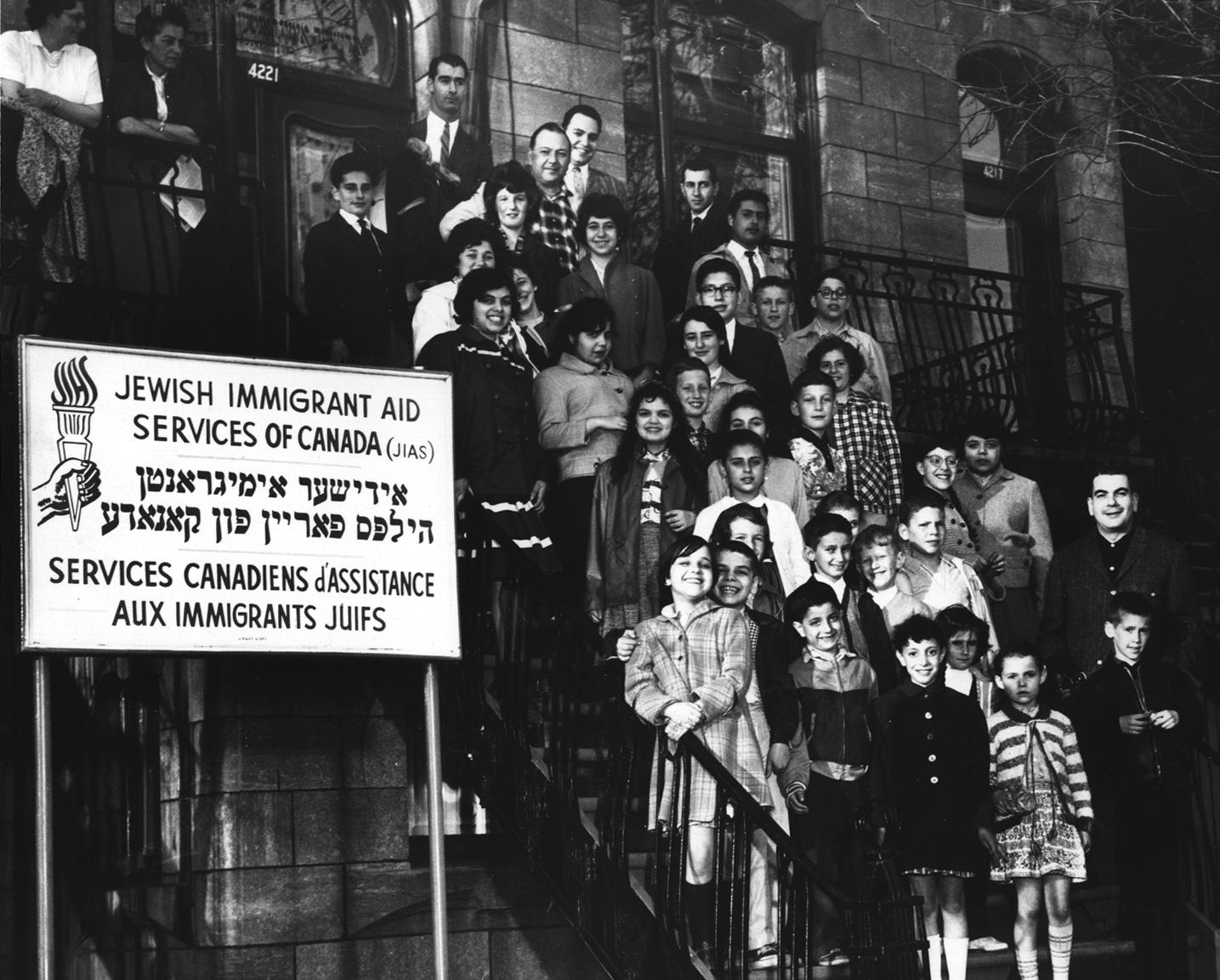 Groupe d'enfants accompagnés d'adultes se tenant dans les escaliers d'un immeuble.