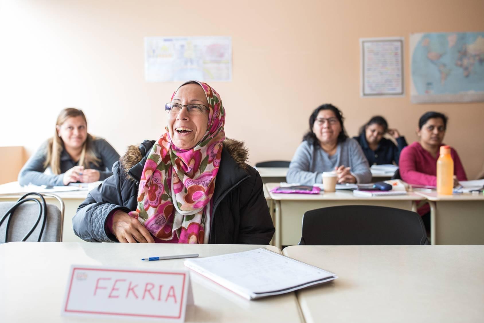 Cinq femmes sont assises à des tables dans une classe.