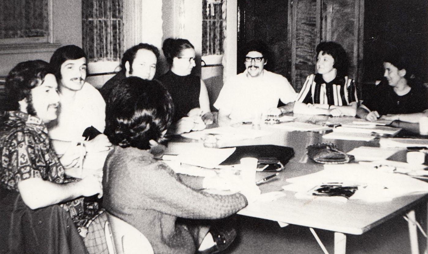 Quatre hommes et quatre femmes sont assis autour d'une table carrée sur laquelle se trouvent des feuilles de papier et des crayons.