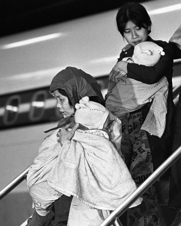 Deux réfugiées vietnamiennes arrivent avec leurs enfants à l'aéroport de Dorval.