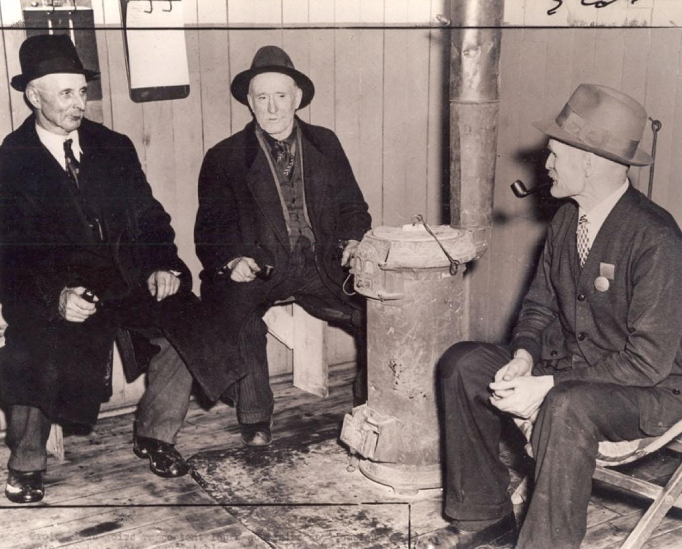 Trois hommes âgés assis autour d'un poêle