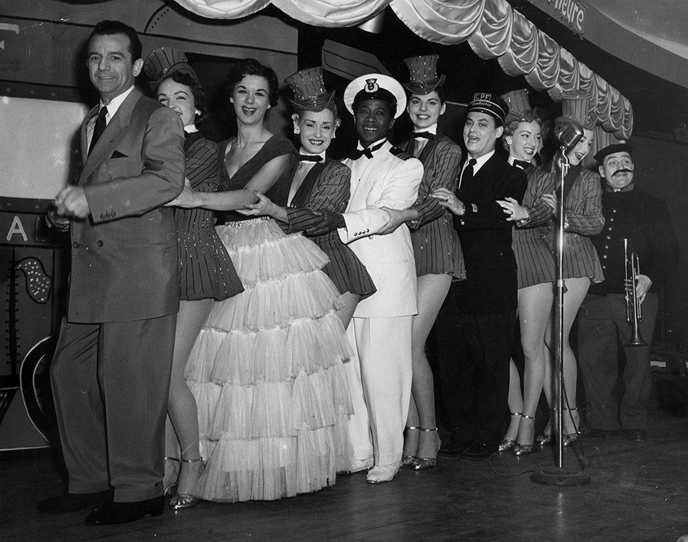 Dix hommes et femmes souriant font la farandole sur une scène de spectacle.